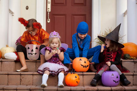 Дети играют в игру Кошелек или жизнь на Хэллоуин