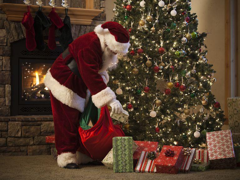 Санта раскладывает подарки под елку на Рождество в Англии