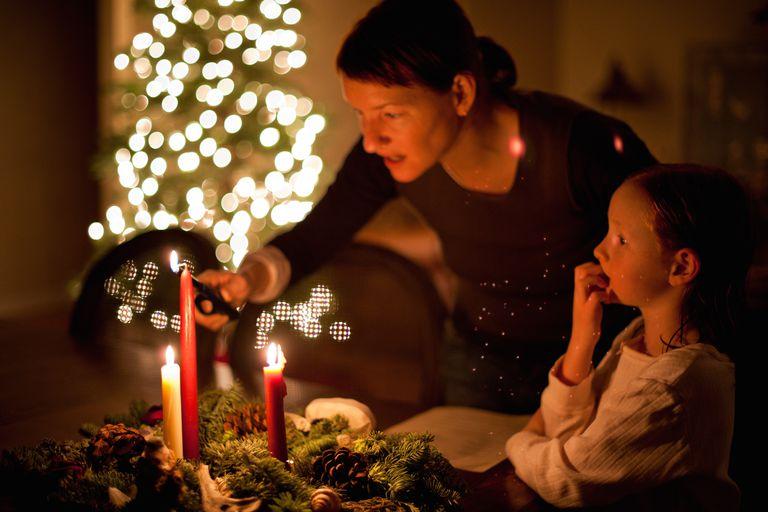 Мама и дочь зажигают свечи на «Advent Wreath» в канун Рождества