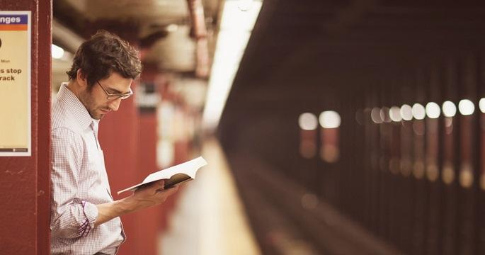 Парень читает английскую книгу на остановке